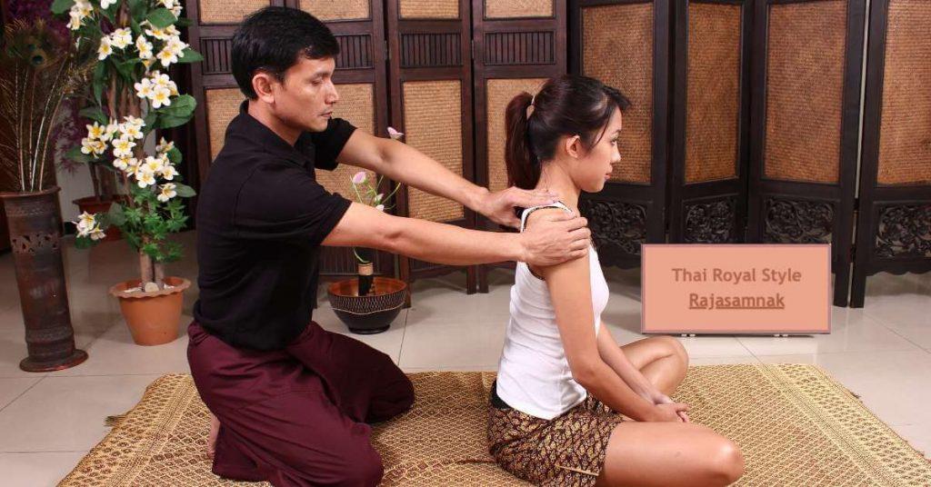 Masajista trabajando en el hombro de una mujer joven, sentados en un futón de un spa durante un masaje tailandés Estilo Real, también conocido como Rajasamnak.