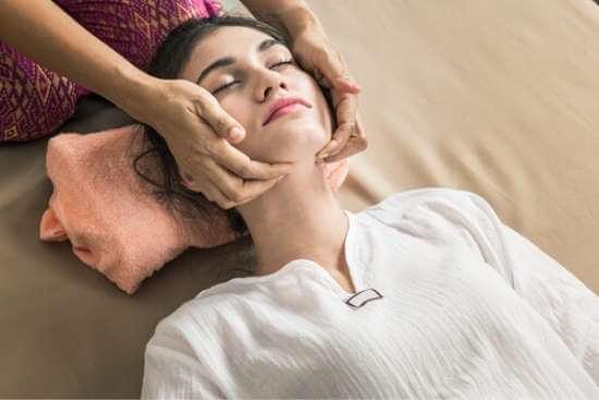 Mujer joven recibiendo un masaje linfático facial Thai. La masajista aplica digitopresión en su cuello, debajo de su mandíbula.