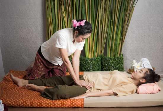Masajista ejerciendo presión con sus palmas al muslo de una clienta durante una sesión de masaje linfático tailandés en un salón.