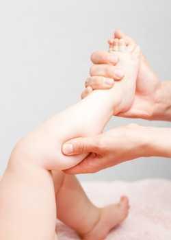 Pantorilla de bebé recibiendo un masaje con estiramiento y digitopuntura.