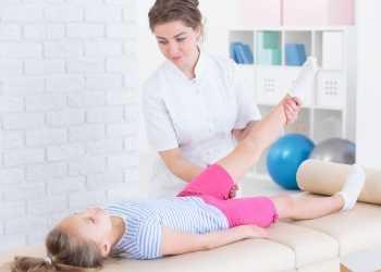 Terapeuta de masaje estirando y moviendo la pierna de una niña de alrededor de 8 años acostada en una camilla.