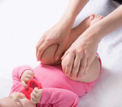 Bebé recibiendo estiramientos de piernas.