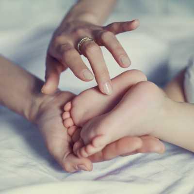 Las plantas de los pies de un bebé siendo acariciados por el dedo de su madre.