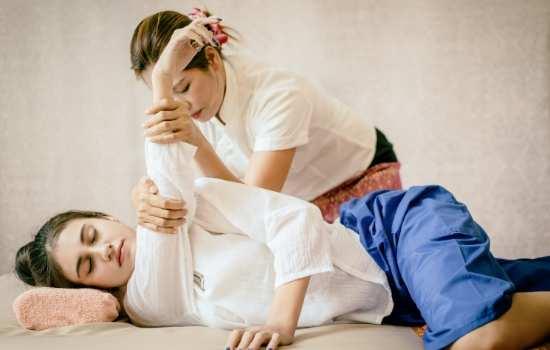 Mujer joven recibiendo un masaje Thai. La masajista estira su brazo derecho para descontracturar el hombro.