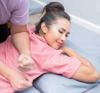 Mujer recibiendo masaje descontracturante Thai en la espalda. Las presiones son realizadas con codos y antebrazos.
