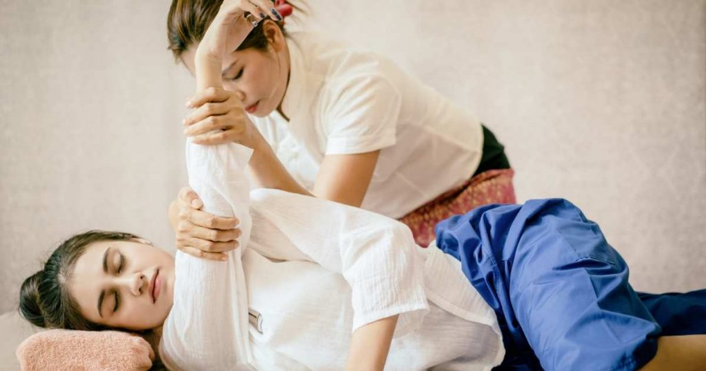 Mujer recibiendo masaje Thai en hombros.