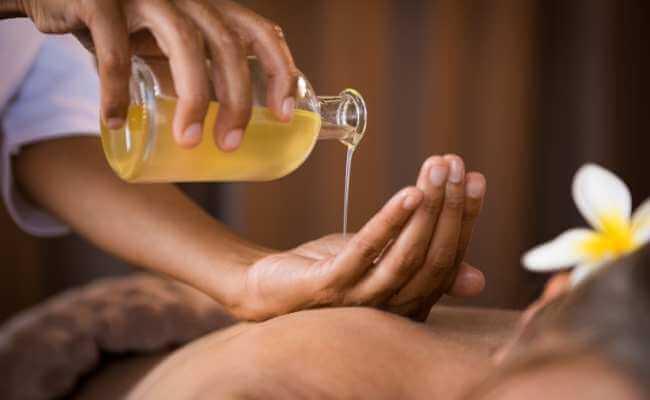 Terapeuta derramando aceite para masaje en su mano.
