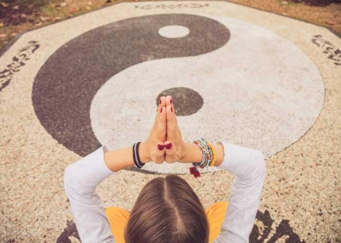Mujer meditando y haciendo ejercicios de estiramientos frente al símbolo del Yin y el Yang.