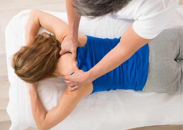 Mujer recibiendo masaje de cuello, hombros y espalda realizado con presiones de dedos.