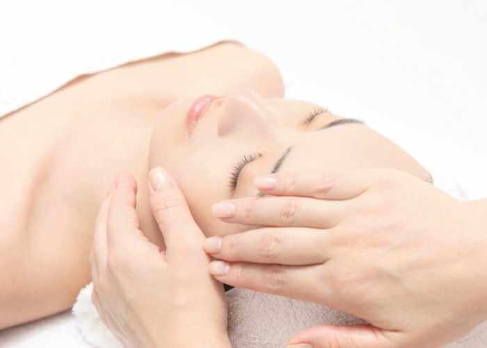 Mujer recibiendo masaje japonés facial suave y antiestrés.