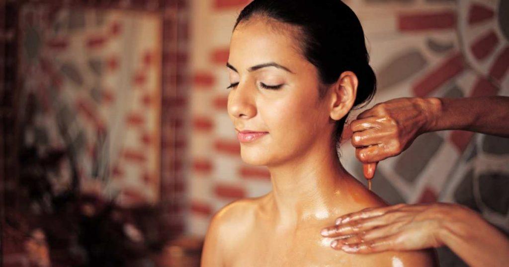 Mujer recibiendo masaje ajurveda con aceites en los hombros.