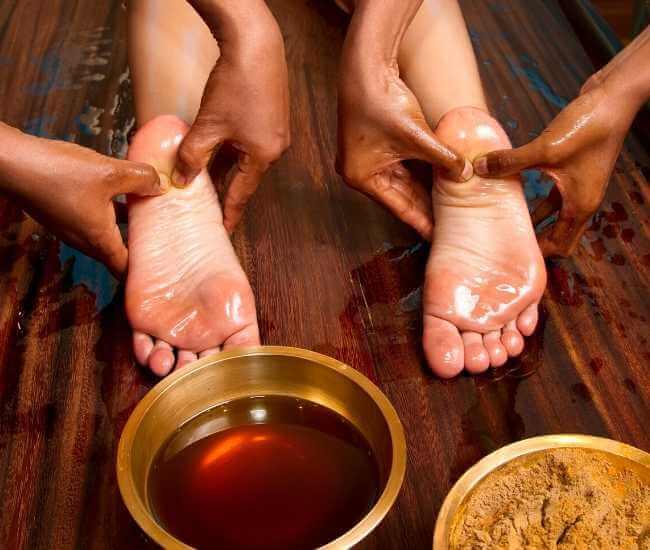 Aceite y polvos aplicados en un masaje podal ajurvédico.