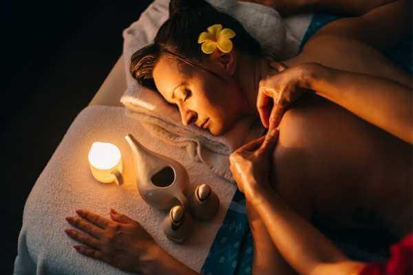 Mujer en spa siendo siendo masajeada con aceites para liberar tensión.