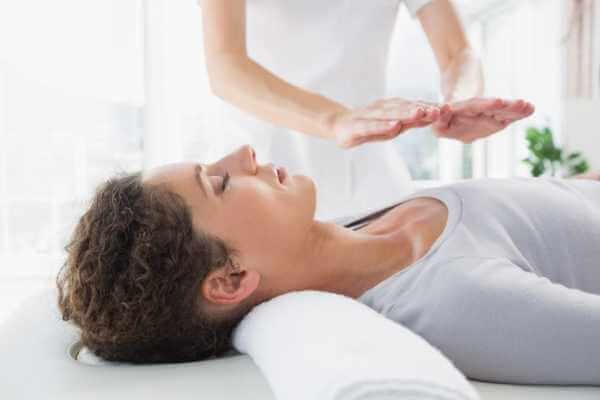 Terapeuta emitiendo energía a paciente durante masaje chino de Chi.