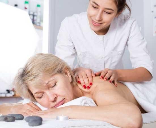 Mujer de edad madura recibiendo masaje relajante en spa