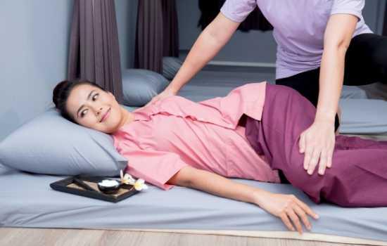 Mujer recibiendo estiramientos de abdomen durante un masaje para gases estilo tailandés.