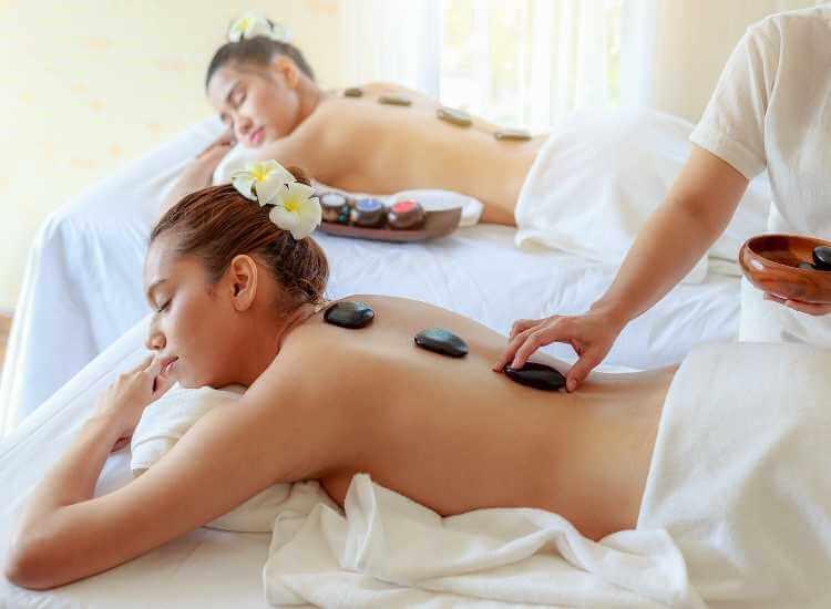 Un par de mujeres disfrutando de una terapia con piedras calientes para la espalda.