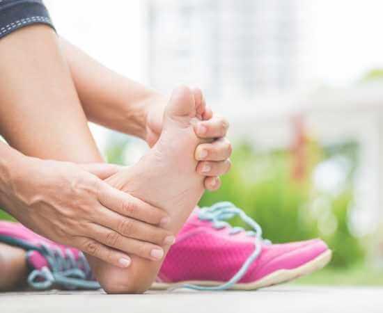 Mujer estirando su pie adolorido después de correr