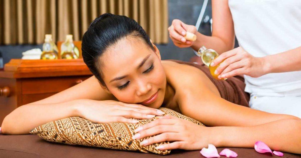 Mujer recibiendo masaje balinés relajante con aceites.