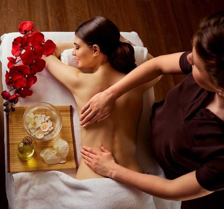Mujer recibiendo tratamiento para espalda con aceites aromáticos.