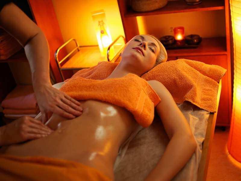 Mujer recibiendo masaje con aceites en el torso para salud digestiva.