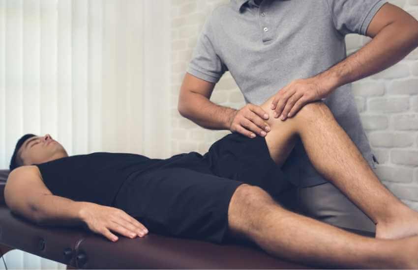 Masajista aplicando digito presión en los músculos de la parte frontal de la pierna