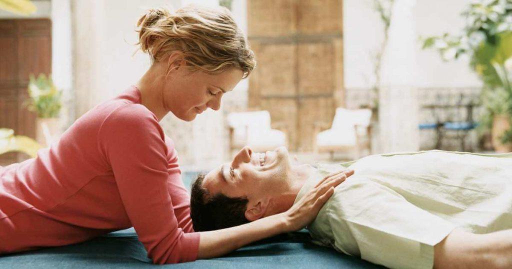 Mujer joven realizando un masaje para hombros para su pareja.