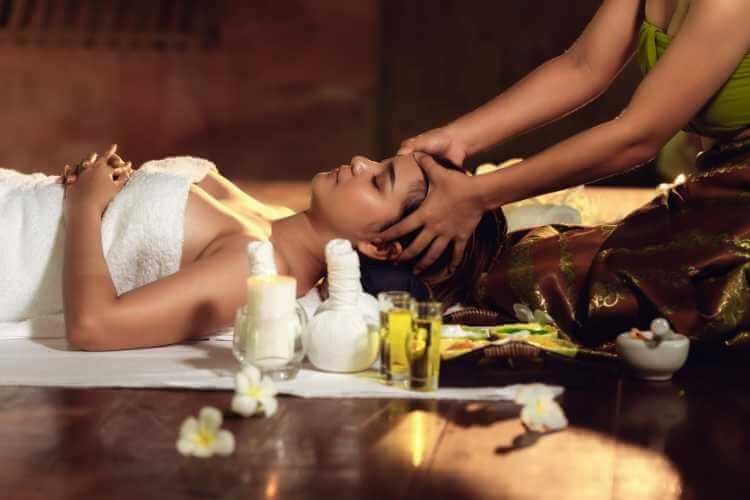 Mujer recibiendo masaje balinés en la frente para belleza facial.