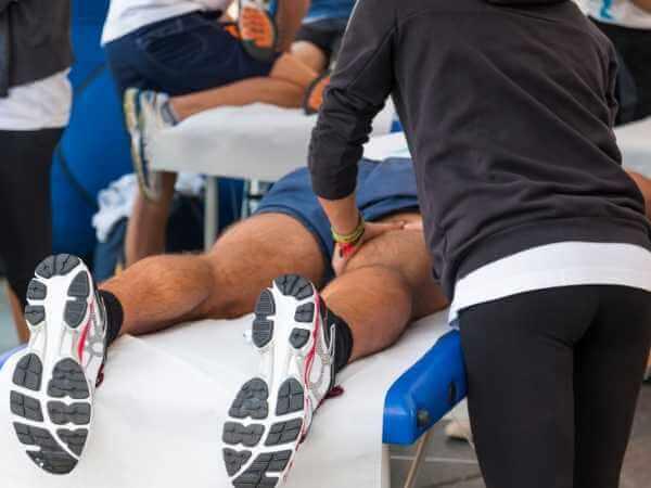 Atletas recibiendo masaje de mantenimiento en grupo.