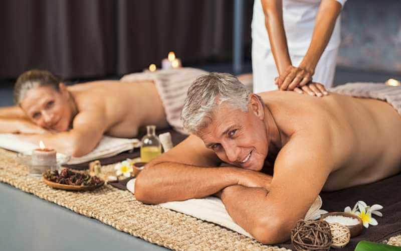 Pareja de adultos mayores recibiendo un masaje romántico para dos.