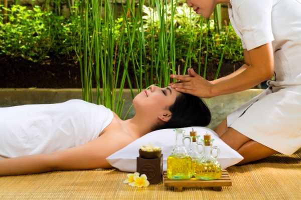 Terapeuta usando los lados de sus manos para realizar percusiones suaves en la cabeza de una joven mujer en spa.