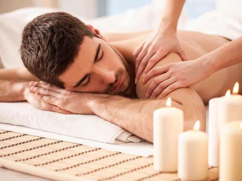 Terapeuta descontracturando los músculos del hombro y zona superior del brazo de un joven.