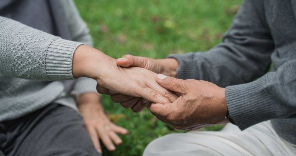 Hombre mayor masajeando la parte superior de la mano de su esposa.