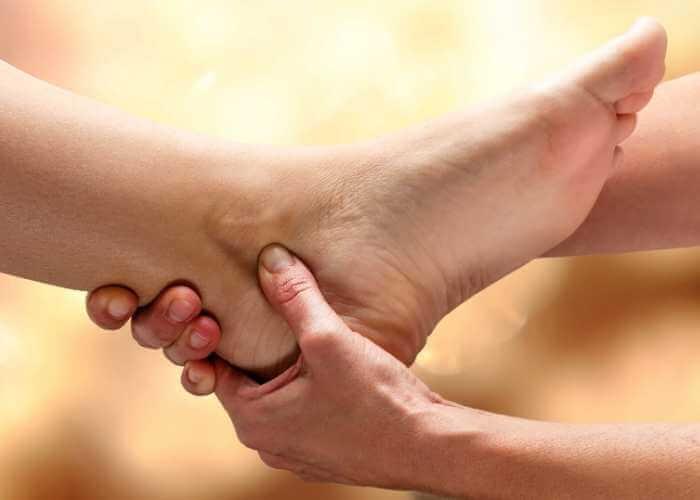 Pie recibiendo terapia de digitopresión en el tobillo.