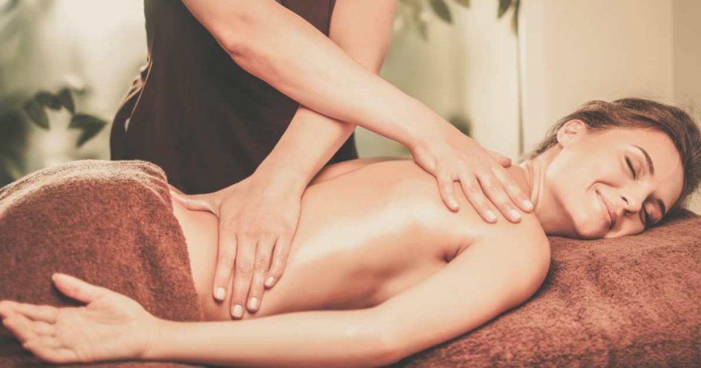 Mujer recibiendo terapia sueca en spa para la espalda con roces de mano.