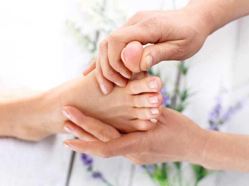 Mujer masajeando el dedo grande y la planta del pie izquierdo de una joven.