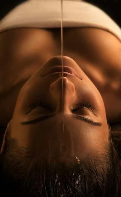 Masaje indio con chorro de aceite cayendo en la frente y el cabello de una mujer joven.