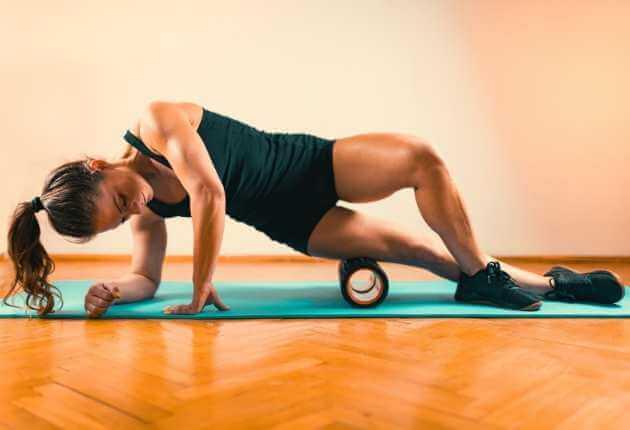 Mujer atlética balanceándose en una colchoneta para realizar un automasaje para el lateral exterior de un muslo usando un rodillo de espuma.