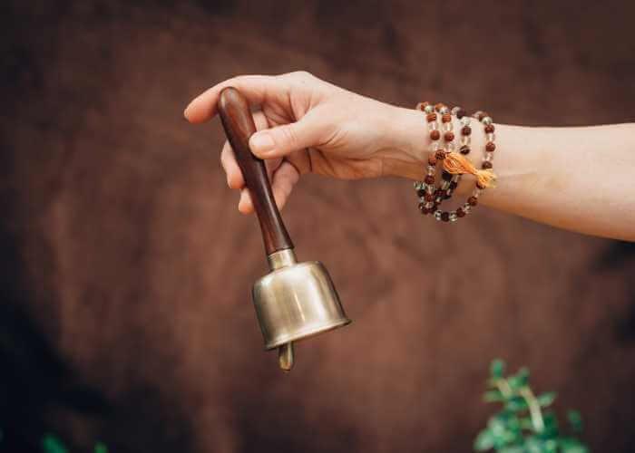 Masajista tocando campaña para inducir estado meditativo y relajante en terapia.