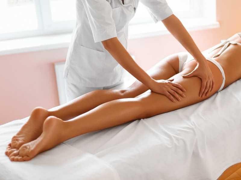Masajista realizando tratamiento para reafirmar y drenar los mulos de su clienta.