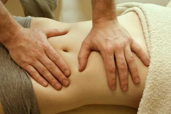 Mujer recibiendo terapia con amasamiento y presiones de palmas para el abdomen.