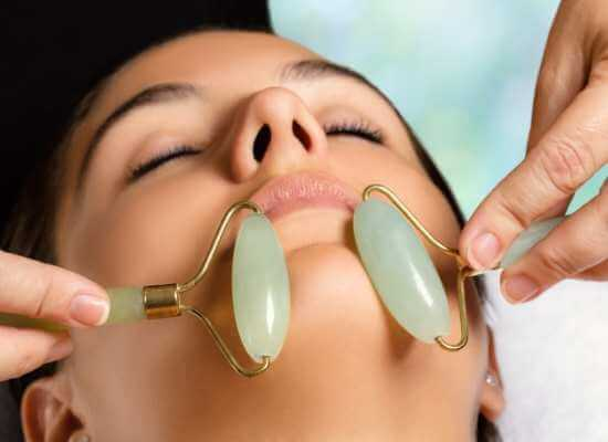 Mujer recibiendo masaje en la barbilla y quijada con dos rodillos de jade.