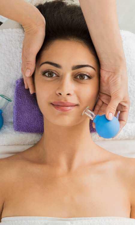 Mujer recibiendo Cupping facial en la mejilla con ventosa plástica con pera de goma.
