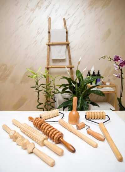 Algunos tipos de rodillos texturizados para Maderoterapia y una copa sueca en una mesa de spa.