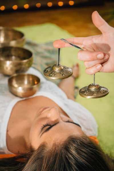 Terapeuta utilizando campanas y platos metálicos para relajar la mente de su clienta.