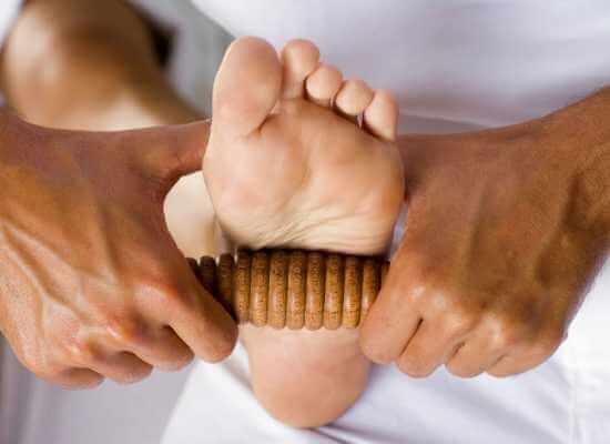 Terapeuta aplicando masaje de reflexología podal con rodillo de madera con relieves.