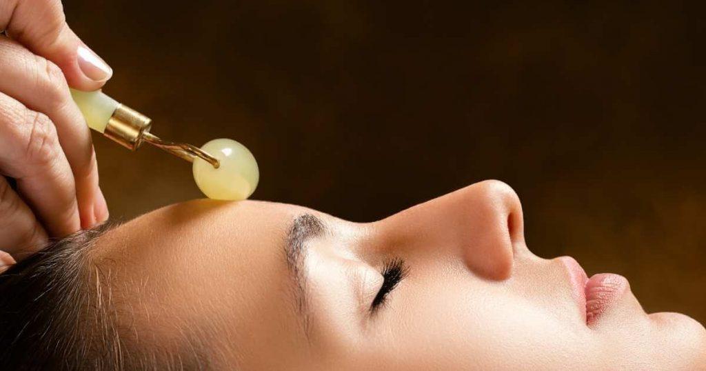 Mujer joven recibiendo un masaje con rodillo de jade en la frente.