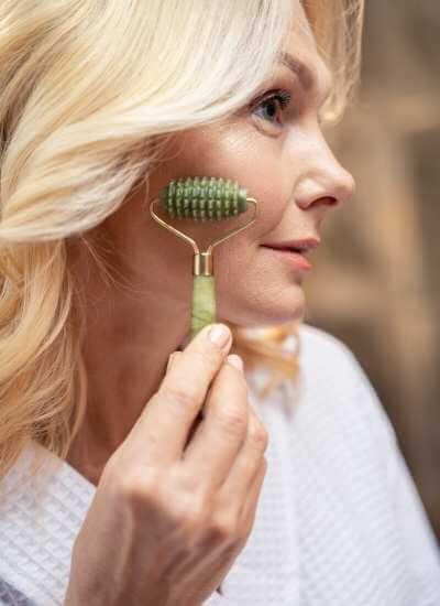 Mujer usando un rodillo facial de jade con relieves.