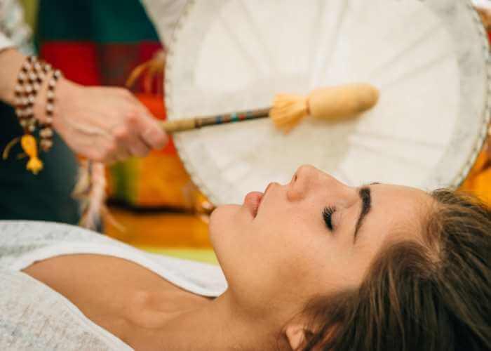 Terapeuta tocando tambor para regular la respiración, energía y ritmo cardíaco de su paciente.