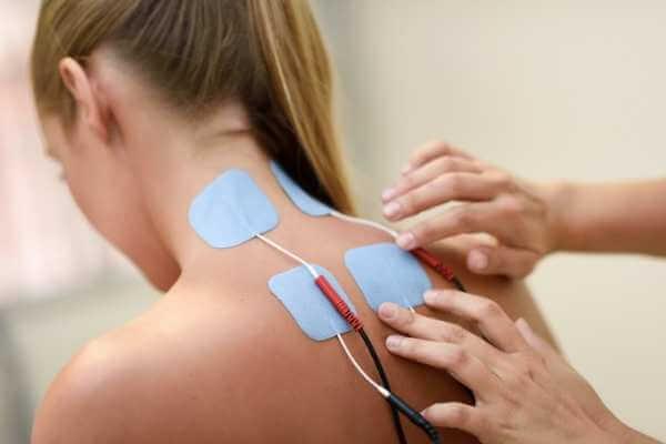 Fisioterapeuta colocando parches con electrodos en el cuello y la parte superior de la espalda de una joven.